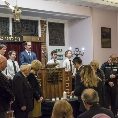 The Rabbi leads the guests in lighting the yahrzeit candles